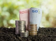 Coins and bank note in soil, saving money concept stock photo