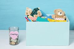 Coins, banknotes in money jar and box with donations. Coins and banknotes in glass money jar with label and a box with donations, charity concept stock image