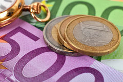 Coins, banknotes and pocket watch Royalty Free Stock Images
