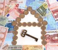 Coins and Banknotes Real State with Key. Banknotes and coins in house shape with key concept for real state royalty free stock image