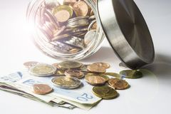 Coins and banknotes spilling from a money jar. With lens flare effect Royalty Free Stock Photography