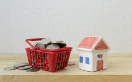 Coins in a basket red and House model Royalty Free Stock Photo