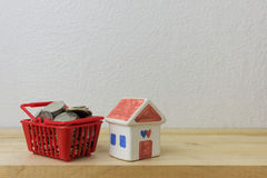Coins in a basket red and House model Stock Images