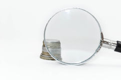 Coins behind magnifying glass stock images