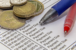 Coins bills pens. Showing a mortgage bill with pens and british coins Royalty Free Stock Photography