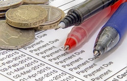 Coins bills pens. Showing a mortgage bill with pens and british coins Royalty Free Stock Images