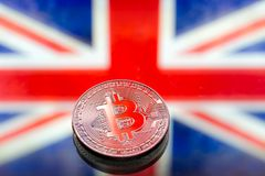 Coins Bitcoin, on a background of Great Britain and the British. Flag, concept of virtual money, close-up. Conceptual image of digital crypto currency Stock Photo