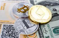 Coins Bitcoin, Litecoin, and Ethereum on the background of the dollar bill. And paper wallet stock photo