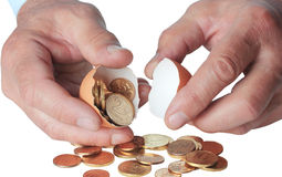 Coins in broken eggshell, in hand Stock Photo