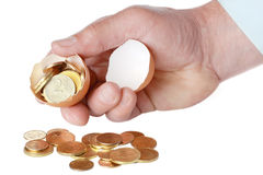 Coins in broken eggshell, in hand Royalty Free Stock Images