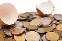 Coins and broken eggshell Royalty Free Stock Images