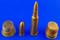 Coins & bullets. Coins and bullets isolated on blue background Stock Photos
