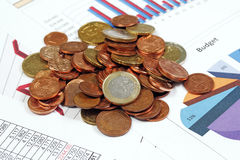 Coins and business charts Stock Images