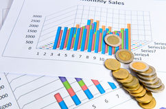 Coins with business data charts or graphs Royalty Free Stock Photo