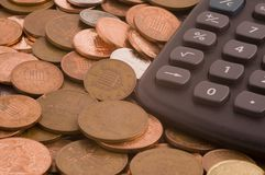 Coins with calculator. Loose change with inset of calculator Royalty Free Stock Images