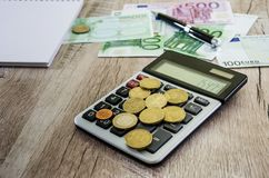 Coins on a calculator against the background of euro and notepad stock photo