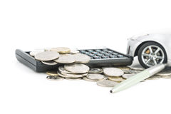 Coins, Calculator, pen and car. A car, calculator, pen and coins  on a white background Royalty Free Stock Images