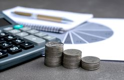 Coins, calculator, pen and graph on table accounting business or. Financial concept Stock Images