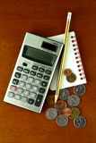 Coins, calculator, pencil and notebook Stock Image
