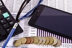 Coins money, calculator, spectacles and mobile phone over a financial report royalty free stock photos
