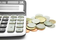 Coins and calculator on white background Royalty Free Stock Photography