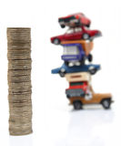 Coins and cars. Pile of coins with pile of cars as background Royalty Free Stock Photography