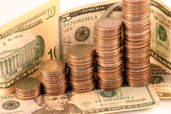 Coins and cash. Ascending coins with cash in the background Stock Image