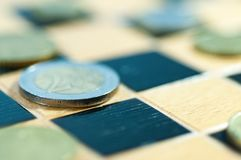 Coins on chess board macro shot. Royalty Free Stock Image