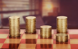 Coins on chessboard. On the background of office space Royalty Free Stock Photo