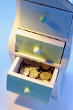 Coins in Chest of Drawers Stock Photography