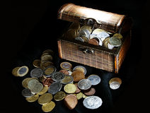Coins in the chest. Money coins in the wooden chest on the black fabric Royalty Free Stock Photography