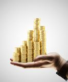 Coins city. Hand holding gold coins city on gray background Royalty Free Stock Photos