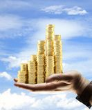 Coins city. Hand holding gold coins city on sky background Stock Photo
