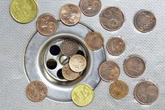 Coins close to drain Royalty Free Stock Photo