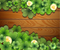 Coins and clover on wooden background Stock Photography