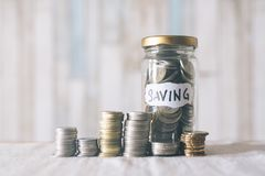 Staked coins and coin jar on a table, Saving and financial concept. Coins and coin jar put on a table.cain jar with & x22;Saving& x22; word attached.saving Royalty Free Stock Photography