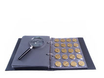 Coins Collection. Conceptual studio isolated photo with album and magnifyer Stock Photo