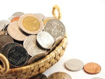 Coins collection in full, on weave basket Royalty Free Stock Image