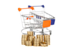 Coins in a column on the background shopping carts. focus on coi Stock Image