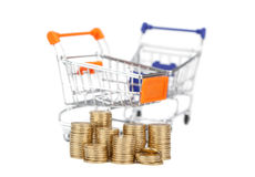 Coins in a column on the background shopping carts. focus on coi Royalty Free Stock Photos