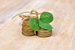 Coins in columns with green clover leaf on wood table Stock Photo