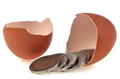 Coins coming out of an eggshell royalty free stock photography