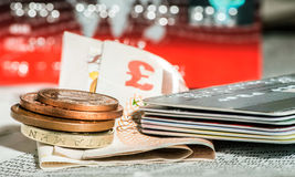 Coins, credit cards and british pounds on newspaper Stock Images