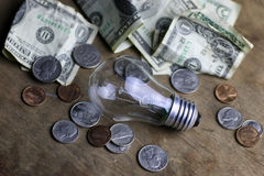 Coins and crumpled money tungsten lamp Stock Photography