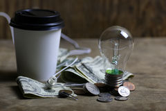 Coins and crumpled money tungsten lamp filament Royalty Free Stock Images