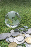 Coins and crystal globe Royalty Free Stock Photo