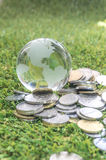 Coins and crystal globe Royalty Free Stock Photography
