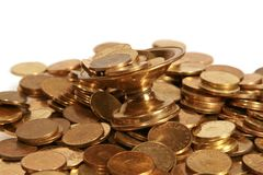 Coins in the cup. Image with many coins in a cup and around it, symbolizing richness Royalty Free Stock Photography
