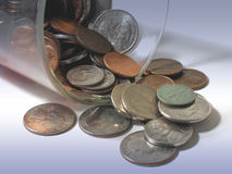 Coins in a cup. Glass of American coins, spilled out royalty free stock photo