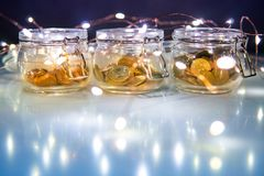 Coins in currency glass jar with Christmas lights royalty free stock images